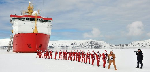 Members of the Royal Navy icebreaker HMS Protector dressed as Santa Claus and Rudolf pose during a charity run off Antarctica